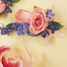 Clusters of blue delphinium are paired with two peach roses.