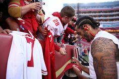 Colin Kaepernick Photos Photos - Colin Kaepernick #7 of the San Francisco 49ers signs an autograph for a fan prior to playing the Los Angeles Rams in their NFL game at Levi's Stadium on September 12, 2016 in Santa Clara, California. - Los Angeles Rams v San Francisco 49ers