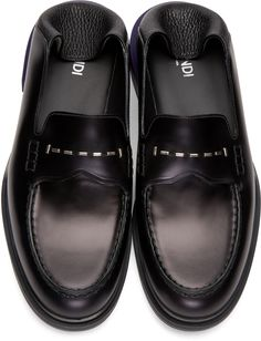 Buffed calfskin loafers in black. Round moc toe. Metal plaque detailing in silver-tone at vamp. Tonal grained deerskin collapsible heel. Stacked heel in purple. Rubber outsole in black. Tonal stitching.