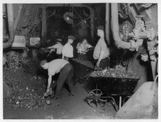 A photograph shows one of the Titanic's coal bunkers filled with workers. This image was taken prior to the Titanic's maiden voyage.