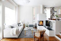 Kiertoilmatakka on teetetty, samoin tv-taso. Telkkarin molemmin puolin on Harri Koskisen suunnittelemat Lantern-kynttilälyhdyt. Takka varaa hieman lämpöä. Leveä sohva on Interfacen mallistosta. Rottinkinojatuoli on äidin isovanhemmilta. Lasipöytä ja sarjapöydät ovat Artekista. Contemporary, Decor, Furniture, Home, Contemporary Rug, Home Decor