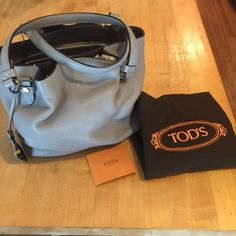 """Grey Tod's Medium Flower Bag This is an excellent Tod's Bag in Grey with silver hardware. Amazing condition-minimal scratches on hardware and one scratch on leather-look at last photo, top right. It is a current piece selling at $1500 and I really prefer a larger bad. It's 12 1/2"""" long and 9"""" inches tall with a shoulder drop of 8 1/2"""". Super soft leather that smells amazing! The side pockets that give it the flower shape are great for keys and sunnies. No Trades! Firm on the price…"""