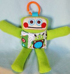 Rudy Robot is so adorable! Hes made from soft green fleece fabric with a front pocket made from a robot print cotton fabric. He is stuffed with non allergenic poly fill and his face is machine appliqued. Rudy Robot is child friendly, there are no buttons & ribbons are sewn to body, he is safe for toddlers & infants. Measures 11 inches tall. READY TO SHIP
