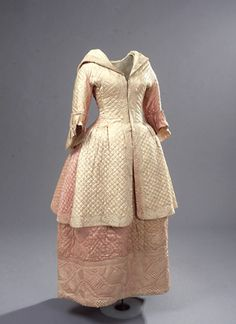 """Quilted pink silk morning dress or negligée (front), Danish, c. 1775. It was not unusual for an upscale woman to receive visitors before and during her morning toilette -- the hours-long process of getting her hair done and her clothing on. A morning dress like this one allowed her to receive both male and female visitors while sitting in bed or in her dressing room."""