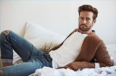 Connecting with OUT, Armie Hammer wears a Stella McCartney cardigan, John Varvatos henley, and Frame Denim jeans.