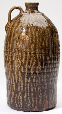 """Georgia Pottery Jug Henry Newton Long(Crawford County, 1858-1907), alkaline glazed one gallon stoneware of a khaki tone with dark olive vertical drips, """"HNL"""" stamp to handle. Actual capacity over one gallon."""