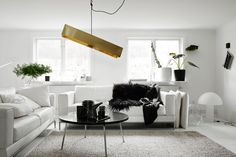 30 Black And White Decor Ideas For A Super Chic Space In this Stockholm home from Annaleena, a white living room is accented with a black table, black faux fur and a striking geometric light fixture.  Saved from:http://www.elledecor.com/design-decorate/color/news/g2968/25-black-white-interiors/?slide=5