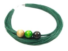 Kolekcja EcoWood Naszyjnik wykonany na bazie przędzy lnianej koloru zielonego bardzo dobrze zaimpregnowanej, na której umieszczono na stałe (nie zmieniają miejsca) korale drewniane, bukowe...