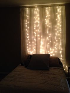 String lights behind sheer curtain headboard