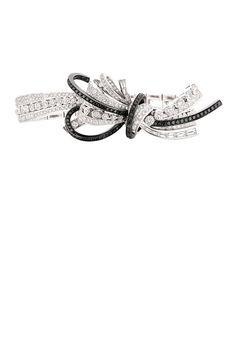 The Ruban Couture bracelet in 18K white gold set with 382 round-cut diamonds, 10 baguette-cut diamonds, and 94 brilliant-cut black diamonds.   - ELLE.com