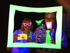 """Photo booths with props are popular now at parties. We decided to try a Blacklight photo booth outside at night. Search Pinterest for """"photo booth printables"""". Print or trace on to phosphorescent neon colored poster board and affix sticks (we used BBQ bamboo skewers) to the back of props. Hang a frame then hang two vertical black lights about 1 1/2 feet in front of the frame, nearly frame width apart. Use a low light/low f-stop 1.8 camera lens or an iPhone with the flash off to take the…"""