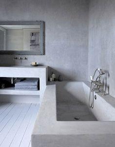 Du béton ciré sur les murs d'une salle de bain avec baignoire