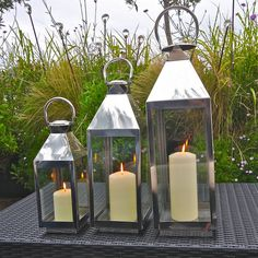 A glass and chrome hurricane lantern perfect for alfresco dining and outdoor living.3 sizes available BUY A SET OF 3 AND SAVE £10Ideal for a coastal setting, the St Ives hurricane lantern is perfect for lighting up your summer bbqs and sheltering the candle or tea light from the wind. The shiny chrome handle and fittings gives it a smart, nautical feel as well as being practical. The lantern can be hung from a pole (not included) or placed on a flat base and has a hinged door to insert ...