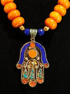 Asia meets Africa in this handsome necklace, featuring a double-sided Hamsa or Khamsa from Morocco and handsome copal beads from Nepal. It is a