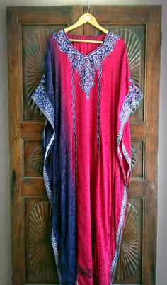 Inject a breathe of exotic flair and ethnic stylishness into your wardrobe with this embroidered japon silk kaftan. Custom handmade to perfection, this caftan maxi dress is simple yet elegant. It features a beautiful japon silk fabric that cascades into an ombre color palette of purple and fuchsia. The long billowing sleeves are the epitome of luxury. Just imagine slipping into this after a soak in a warm bubble bath or wearing it the next time you host a dinner party. The styling…