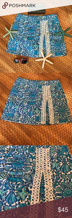 """Lilly Pulitzer Skort Must Have Summer Skort By Lilly Pulitzer! Size:10. Gently worn about once. EUC. Colors are white & different shades of blue with different types of sea shells. Shorts underneath are white. Back zip closure. 2 side pockets. Feel confident this summer at amusement parks, on vacation, BBQ etc because of the Skort & feel cool at the same time ! Add a simple Tee & flip flops you ready for your summer adventure! Length approx 16"""". Machine wash tumble dry. NO TRADES. Lilly…"""