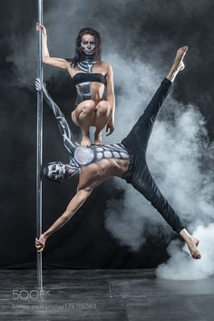 Posing of pole dance couple in dark studio by bezikus