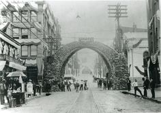 "A huge coke arch stretches across the width of a street. On the top of the arch is a sign that reads: HCFC Co. People are standing under and to either side of the arch, as well as along the city street. Directly underneath the center of the arch, a young boy kneels with his arms around his dog's neck. Banners and flags hang from the buildings. To the right of the photograph are vendors and a large barrel that reads ""ice water"". Almost every man on the street wears a suit and a hat. In the…"