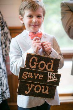 This signage says so much! Sweet sentiment and awesome twist to a traditional ring pillow. | Photo: Eric Boneske.