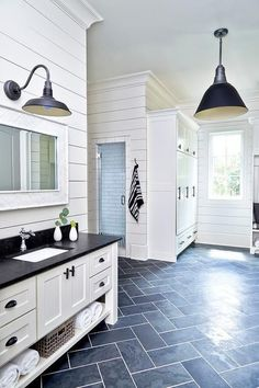 Black and white cottage mudroom is clad in dark slate herringbone floor tiles lit by a black vintage bar pendant and boasts a white washstand finished with oil rubbed bronze cup pulls, a shelf, and a honed black marble countertop fitted with an undermount sink and polished nickel faucet.
