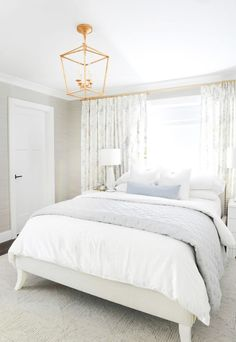 White and gray bedroom featuring a light gray bed with a low headboard dressed in white and gray bedding in front of a window. White and gray bedroom featuring a light gray bed with a low headboard dressed in white and gray bedding in front of a window. Bed Against Window, Window Above Bed, Window Bed, Bed Without Headboard, White Headboard, Grey And White Bedding, Grey Bedding, Rustic Bedding, Transitional Bedroom