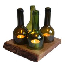 Allium Upcycle Wine Bottle Candle Holder: Allium Upcycle creates pretty and unusual decorative products from recycled materials. All glass is cut and sanded to ensure edges are completely smooth, while the solid oak blocks are left with a waney edge, ensuring a completely unique look for each individual item. The Wine Bottle Candle Holder consists of four recycled bottles resting on a beautiful piece of wood holding four tea light. The green bottles look great when lit up.