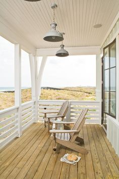 This second-floor Gulf-front porch with two Adirondack chairs facing the water is an ideal spot from which to watch the sun rise and set. The horizontal rail, rather than conventional vertical pickets, provides a seamless view.    Tour the Tarpon Run Idea House