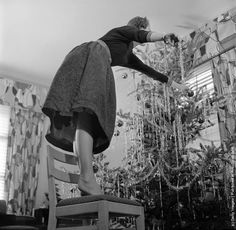 When decorating a Christmas tree use a firm stepladder and don't be like this woman who is standing on a chair and leaning over too far. (Photo by Orlando /Three Lions/Getty Images). Circa 1955.