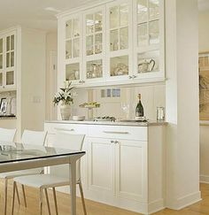 Glass cabinets as pass-through, built-in cabinets on dining room side of peninsula.