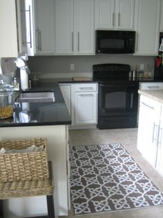 Example Of Oak Cabinets Painted White: After. Black counters w/black appliances