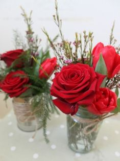 Cute jam jar and a rustic tin with red Roses, seasonal red flowers and foliage. Presented in a gift bag with red rose petals