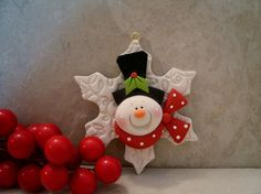 A happy snowman on a frosty flake!    This is an original design that has been handcrafted from polymer clay. The ornament measures approximately 3 1/2 in diameter. All parts have been secured with liquid polymer for increased strength and the piece was lightly glazed with a satin glaze. It will hang from a jute hanger.    Not a toy...not suitable for young children.