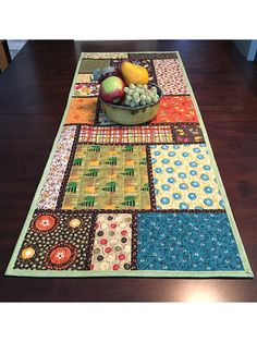 "This table runner is a great project for using up leftover fabrics in a variety of ways. Use fussy-cut prints all in the same subject, or use different prints all in 1 color scheme. It would also look pretty with batiks in various colors, with black sashing, for a stained glass look. Size: 18"" x 45"". Skill Level: Easy"