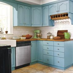 Hints of gray give this aqua shade depth and charm, updating the traditional styling of these kitchen cabinets while tying them to the updated stainless-steel appliances. Paint: Kingston Aqua; Olympic