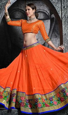 Set the floor ablaze with this orange shade net flared lehenga choli. The enticing floral patch, lace, resham and stones work a significant element of this attire. Upon request we can make round front/back neck and short 6 inches sleeves regular lehenga blouse also. #RavishingOrangeColorGagharaCholi