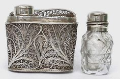 A silver filigree scent bottle holder modeled on a binoculars case and containing original cut-glass scent bottles