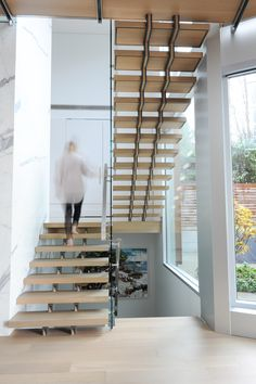 Wooden stairs with a wall of glass creates dramatic lighting and sense of the outside coming in.