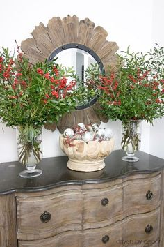 Christmas home tour - a bowl full of ornaments flanked by vases of boxwood branches and berries for entryway Christmas decor #christmas #decorations #foyer
