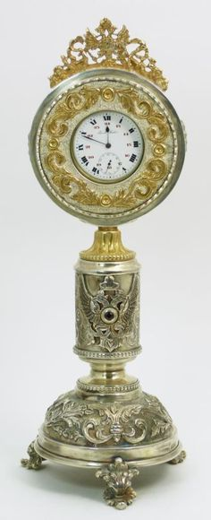 "A Pavel Buhre pocket watch clock. Watch has white enamel face with black Roman numerals at every hour and red Arabic Numerals in five second intervals. Metallic cobalt blue hour, minute and sub second hand. Clock mount has silver and vermeil tones with applique double headed eagle coat of arms and Nicholas II design. Scrolled repousse designs throughout. Mount hallmarked to side of base. Measures 11 1/4"" height (28.5cm)"