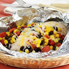 Chicken breasts topped with black beans, corn, and zesty tomatoes, cooked in foil packets on the grill for an easy summertime meal.