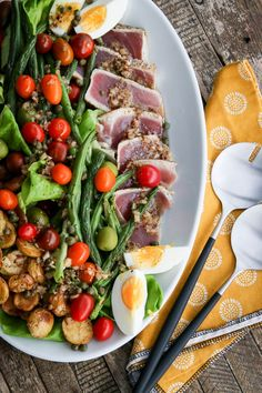 A twist on traditional Nicoise Salad, this dish uses lightly seared ahi instead of canned tuna and oven-roasted potatoes and beans instead of boiled potatoes and steamed beans. The result is a salad for dinner that is suitable for either a weeknight meal or casual entertaining.