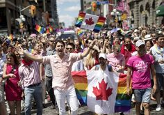 Prime Minister Justin Trudeau waves a rainbow-coloured Canadian flag as he marches in the annual Pride parade in Toronto on Sunday.