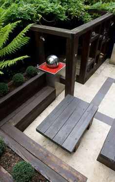 Red mulch provides a punch of colour in this modern courtyard garden #moderncourtyard #mulch #waterfeature