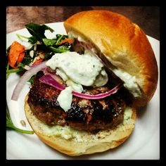 Homemade 8oz Ontario Lamb Burger with Pickled Red Onion, a Feta & Cucumber Sauce and Mixed Green Salad
