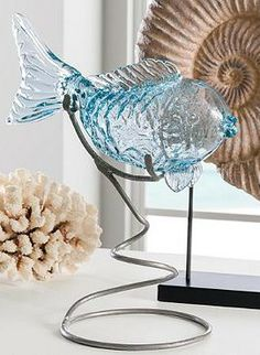 Like poetry in motion for your shelf, sideboard, or mantel, our clear blue glass koi rests swimmingly upon a spiral metal stand or upon its own fins.