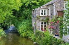A quaint, old English cottage on the bank of a small river in Cartmel, Cumbria, England