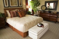 Geometric wood paneled dressers highlight this bedroom with cream sheets, white ottoman, and square patterned carpet.
