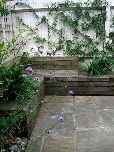 Corner Seating Area in London Garden, Gardenista. Stacked oak sleepers create seating and raised beds.