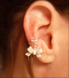 So, I'm clearly developing an obsession with ear cuff, but c'mon... It's adorable. Ear Cuff, Dainty and Feminine Silver Cuff with White Bow Charm. $8.95, via Etsy.