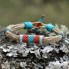 This colorful ethnic bracelet made of linen string and high quality Japanese seed beads in blue, red and teal is absolutely unique. I designed this